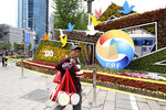 A man selling Chinese drums walk past a decoration promoting the upcoming Road and Belt Forum in Beijing on Friday, April 19, 2019. China is downplaying the political implications of its global development campaign known as the Belt and Road initiative, saying that it aims to boost multilateralism amid protectionist trends in the U.S. and elsewhere. (AP Photo/Ng Han Guan)