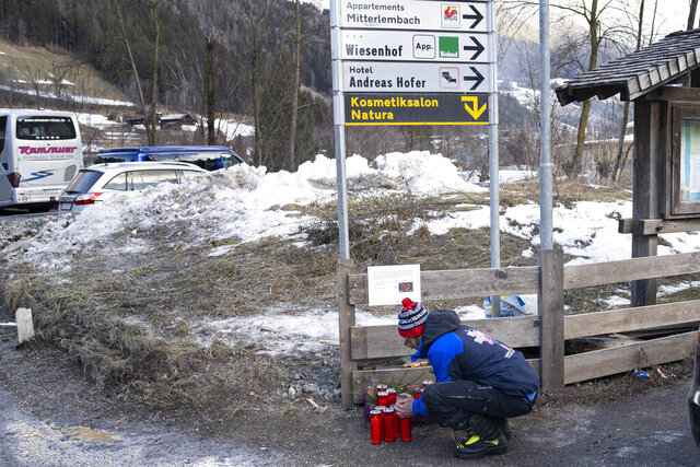 A man lights a candle at the scene where a car has plowed into a group of people in Luttach, near Bruneck in the northern region South Tirol, Italy, Sunday, Germany, Jan. 5, 2020. Italian fire officials say a car has plowed into a group of young German tourists in northern Italy, killing at least six people and injuring eleven. (AP Photo/Helmut Moling)