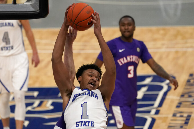 Indiana State's Tre Williams (1) reaches for a rebound as Evansville's Jawaun Newton (3) watches during the second half of an NCAA college basketball game in the quarterfinal round of the Missouri Valley Conference men's tournament Friday, March 5, 2021, in St. Louis. (AP Photo/Jeff Roberson)