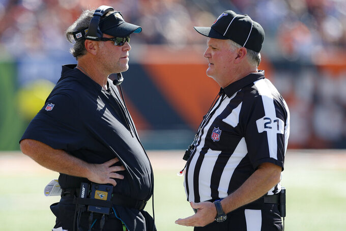 Jacksonville Jaguars head coach Doug Marrone, left, speaks with side judge Jeff Lamberth (21) in the first half of an NFL football game against the Cincinnati Bengals, Sunday, Oct. 20, 2019, in Cincinnati. (AP Photo/Gary Landers)
