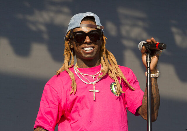 FILE - In this June 16, 2018, file photo, Lil Wayne performs on Day 3 of the 2018 Firefly Music Festival at The Woodlands in Dover, Del. Rapper Lil Wayne has been charged with possession of a firearm by a convicted felon, an offense that carries a potential sentence of up to 10 years in prison. Documents filed Tuesday, Nov. 17, 2020,  in Miami federal court say the rapper, whose real name is Dwayne Michael Carter Jr., had a gun and ammunition on Dec. 23 of last year despite knowing he had the previous felony.  (Photo by Owen Sweeney/Invision/AP, File)