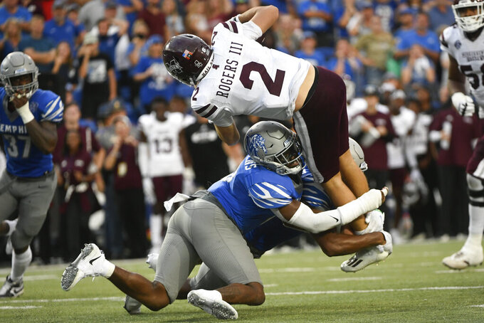 Mississippi State quarterback Will Rogers (2) is stopped short of the goal by Memphis linebacker Xavier Cullens, bottom front, and defensive back Quindell Johnson, bottom back, during a two-point conversion-attempt during the closing moments of an NCAA college football game on Saturday, Sept. 18, 2021, in Memphis, Tenn. (AP Photo/John Amis)