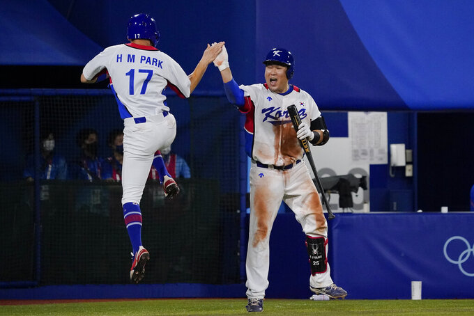 South Korea's Hae Min Park (17) and Euiji Yang celebrate during the ninth inning of a baseball game against the Dominican Republic at the 2020 Summer Olympics, Sunday, Aug. 1, 2021, in Yokohama, Japan. (AP Photo/Sue Ogrocki)