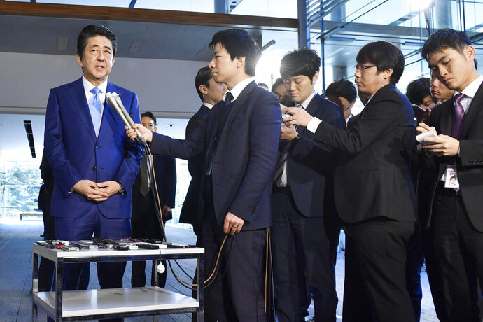Japan's Prime Minister Shinzo Abe, left, speaks to media at his office Wednesday, Nov. 20, 2019, in Tokyo. Abe has made history by becoming Japan's longest-serving political leader, though he hasn't achieved his biggest goal of revising the nation's pacifist constitution. (Kyodo News via AP)