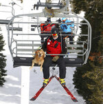 Ski patrol dog Buster rides the lift with his handler, patroller Andrew Pinkham, at Sugar Bowl Resort in Norden, Calif. on March 17, 2021. Rescue dogs at Lake Tahoe ski resorts receive specialized training to rescue people from avalanches in Nevada and California. They're trained to detect human scents, find buried clothes and rescue people sunk 10 to 12 feet (3 to 3.7 meters) in the snow. (Jason Bean/The Reno Gazette-Journal via AP)