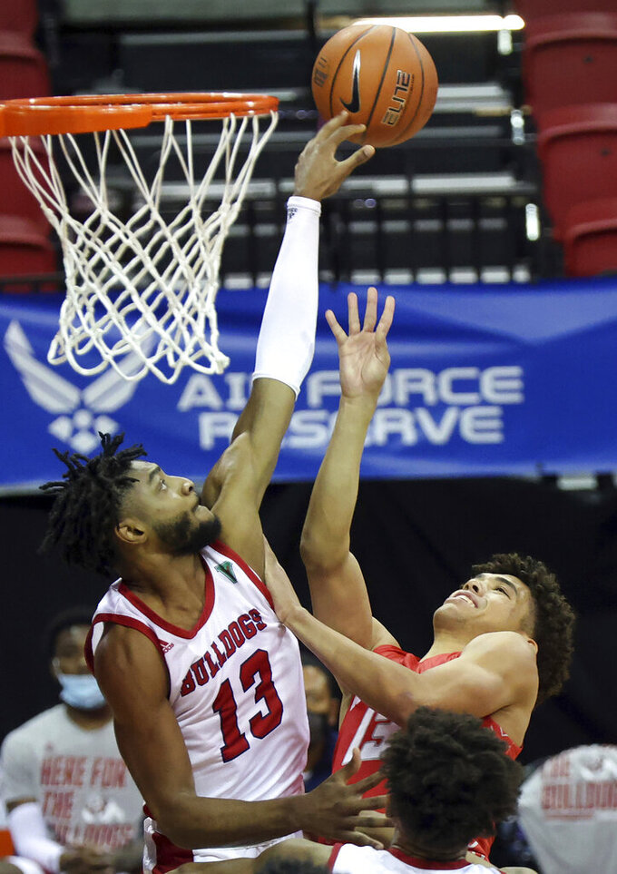 New Mexico guard Javonte Johnson (13) shoots as Fresno State guard Deon Stroud (13) defends during the first half of an NCAA college basketball game in the first round of the Mountain West Conference men's tournament Wednesday, March 10, 2021, in Las Vegas. (AP Photo/Isaac Brekken)