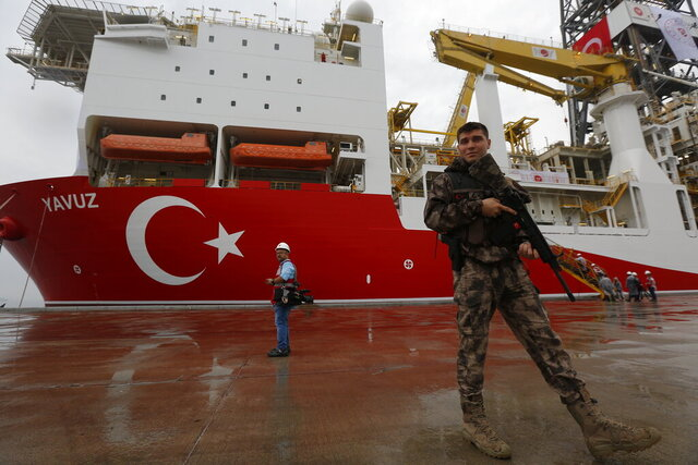 FILE - In this Thursday, June 20, 2019 file photo, a Turkish police officer patrols the dock, backdropped by the drilling ship 'Yavuz' to be dispatched to the Mediterranean, at the port of Dilovasi, outside Istanbul.  The leaders of Greece, Israel and Cyprus are set to sign a deal Thursday Jan. 2, 2020, for a 1,900-kilometer (1,300-mile) undersea pipeline that will carry gas from new offshore deposits in the southeastern Mediterranean to continental Europe. (AP Photo/Lefteris Pitarakis, File)