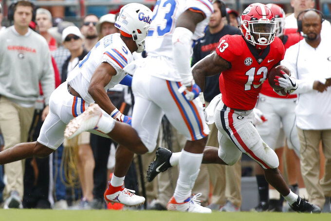 Georgia tailback Elijah Holyfield (13) moves the ball down the field during the first half of an NCAA college football game between Georgia and Florida at in Jacksonville, Fla. Saturday, Oct. 27, 2018. (Joshua L. Jones/Athens Banner-Herald via AP)