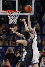 Gonzaga forward Drew Timme, right, shoots over Santa Clara forward Guglielmo Caruso during the second half of an NCAA college basketball game in Spokane, Wash., Thursday, Feb. 25, 2021. (AP Photo/Young Kwak)
