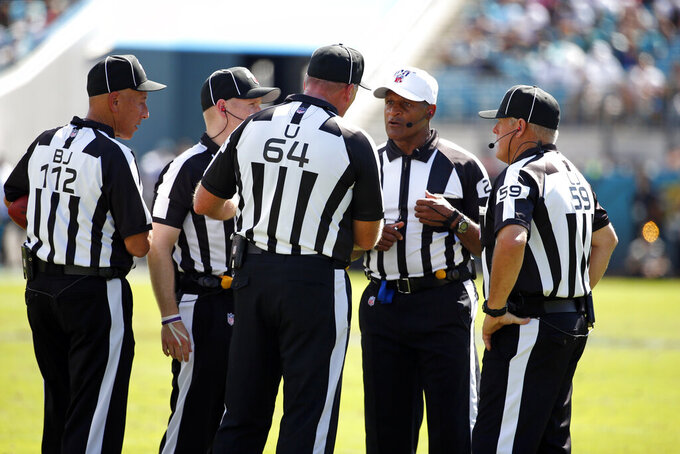 Officials discuss a ruling during the first half of an NFL football game between the Jacksonville Jaguars and the New Orleans Saints, Sunday, Oct. 13, 2019, in Jacksonville, Fla. (AP Photo/Stephen B. Morton)