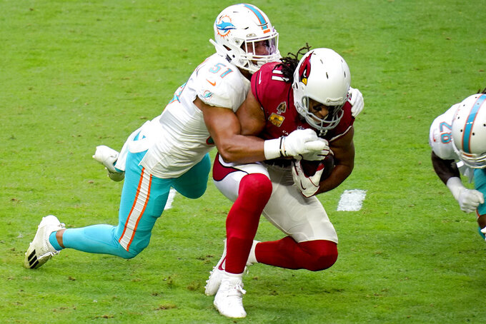 Arizona Cardinals wide receiver Larry Fitzgerald (11) makes the catch as Miami Dolphins outside linebacker Kamu Grugier-Hill (51) makes the tackle during the first half of an NFL football game, Sunday, Nov. 8, 2020, in Glendale, Ariz. (AP Photo/Ross D. Franklin)