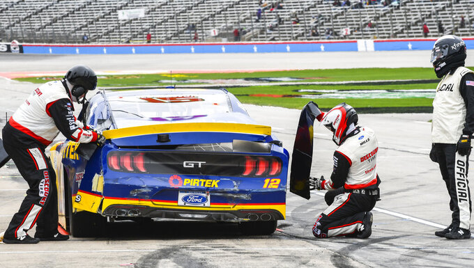 Members of Brad Keselowski's pit crew make repairs to his car as a NASCAR official looks on during a NASCAR auto race at Texas Motor Speedway, Saturday, March 30, 2019, in Fort Worth, Texas. (AP Photo/Randy Holt)