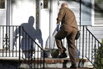 In this Nov. 26, 2019, file photo a UPS man delivers an Amazon package to a residence in North Andover, Mass. Amazon, Walmart and others are promising to deliver more of their goods in a day and this holiday season will be the first real test of whether they can make that happen. (AP Photo/Elise Amendola)