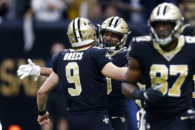 New Orleans Saints quarterback Drew Brees (9), right, hugs wide receiver Tre'Quan Smith after the two connected on a touchdown pass, where Brees tied Peyton Manning for the NFL record for mist career touchdown passes in the first half of an NFL football game against the Indianapolis Colts in New Orleans, Monday, Dec. 16, 2019. (AP Photo/Butch Dill)