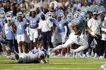 North Carolina quarterback Sam Howell (7) evades Georgia State linebacker Jordan Veneziale (40) as he runs for a touchdown during the first half of an NCAA college football game in Chapel Hill, N.C., Saturday, Sept. 11, 2021. (AP Photo/Chris Seward)