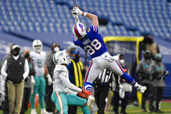 Buffalo Bills tight end Dawson Knox (88) catches a pass in front of Miami Dolphins free safety Eric Rowe (21) in the second half of an NFL football game, Sunday, Jan. 3, 2021, in Orchard Park, N.Y. (AP Photo/Adrian Kraus)