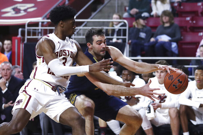 Boston College guard Jared Hamilton (3) tries to stop Notre Dame forward John Mooney, right, on a drive to the basket during the first half of an NCAA men's college basketball game in Boston, Wednesday, Feb. 26, 2020. (AP Photo/Charles Krupa)