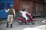 "A Kashmiri man requests a paramilitary soldier to let him through during curfew in Srinagar, Indian controlled Kashmir, Tuesday, Aug. 4, 2020. Authorities clamped a curfew in many parts of Indian-controlled Kashmir on Tuesday, a day ahead of the first anniversary of India's controversial decision to revoke the disputed region's semi-autonomy. Shahid Iqbal Choudhary, a civil administrator, said the security lockdown was clamped in the region's main city of Srinagar in view of information about protests planned by anti-India groups to mark Aug. 5 as ""black day."