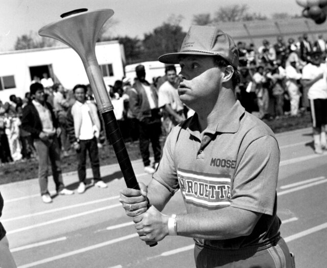 FILE - In this May 11, 1988, file photo, Michael Cusack carries the torch around the track at the University of Chicago's Stagg Field during the Special Olympics opening ceremony in Chicago. Cusack, a Chicago-area man who helped inspire the Special Olympics movement and who won multiple medals at the athletic event over years, has died. He was 64. The Chicago Tribune reported Monday, Dec. 21, 2020, that Cusack, who had Down syndrome, died at Good Shepherd Manor in Momence on Dec. 17 of natural causes associated with Alzheimer's. (Charles Cherney/Chicago Tribune via AP, File)