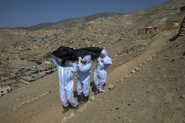Venezuelans Luis Zerpa, from left, Luis Brito and Jhoan Faneite, carry a body bag that contains the remains of 51-year-old Marcos Espinoza who is suspected to have died of the new coronavirus, down a steep hill to a waiting hearse in a working-class neighborhood near Pachacamac, the site of an Inca temple, on the outskirts of Lima, Peru, Friday, May 8, 2020.