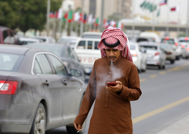 FILE - In this Monday, Dec. 9, 2019 file photo, a man smokes a cigarette as he looks at his mobile phone in Riyadh, Saudi Arabia. On Thursday, Dec. 19, 2019, the World Health Organization said worldwide, the number of men using traditional tobacco products has finally started to decline. (AP Photo/Amr Nabil)