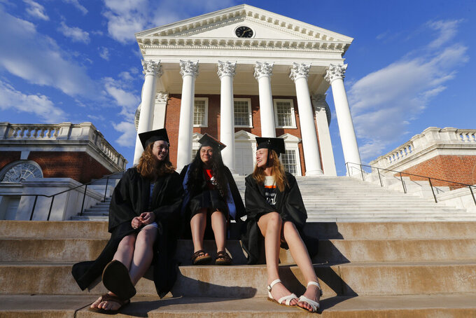 University of Virginia graduates, Madeline Wallach, left, of Middleberg, Va., Alexandra Dimas, of Chesapeake, Va., center, and Laura Chattin, of View, Va., sit on the stairs of the Rotunda on graduation weekend at the school Saturday May16, 2020, in Charlottesville, Va. The school is holding a virtual graduation in light of COVID-19 restrictions. (AP Photo/Steve Helber)