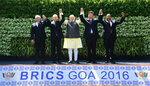 FILE - In this Sunday, Oct. 16, 2016 photo, leaders of BRICS countries, from left, Brazilian President Michel Temer, Russian President Vladimir Putin, Indian Prime Minister Narendra Modi, Chinese President Xi Jinping, and South African President Jacob Zuma raise their hand for a group photo at the start of their summit in Goa, India. Modi and his Bharatiya Janata Party on Thursday, May 23, 2019, claimed a thunderous sweep of India's general elections, winning well over the 272 seats in the lower house of Parliament required to form a government. Modi's vision of India is threefold, political analysts say: getting India into the exclusive $5 trillion economy club that includes the European Union, United States, China and Japan; asserting itself as a nuclear power and a force in the world; and placing its Hindu heritage at the center of politics. (AP Photo/Anupam Nath, File)