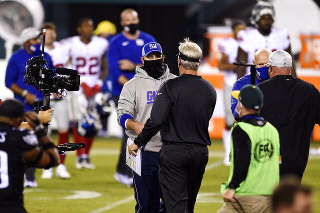 New York Giants head coach Joe Judge, left, and Philadelphia Eagles head coach Doug Pederson meet after an NFL football game, Thursday, Oct. 22, 2020, in Philadelphia. (AP Photo/Derik Hamilton)