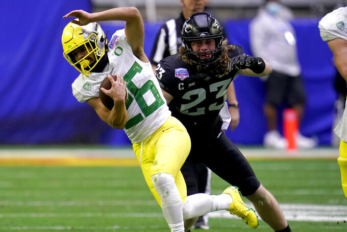 Oregon running back Travis Dye (26) eludes the reach of Iowa State linebacker Mike Rose (23) during the first half of the Fiesta Bowl NCAA college football game, Saturday, Jan. 2, 2021, in Glendale, Ariz. (AP Photo/Ross D. Franklin)