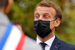 French President Emmanuel Macron wears a protective face mask as he arrives at the 'la Maison des habitants' (MDH) in Les Mureaux, northwest of Paris, Friday, Oct. 2, 2020. President Emmanuel Macron, trying to rid France of what authorities say is a