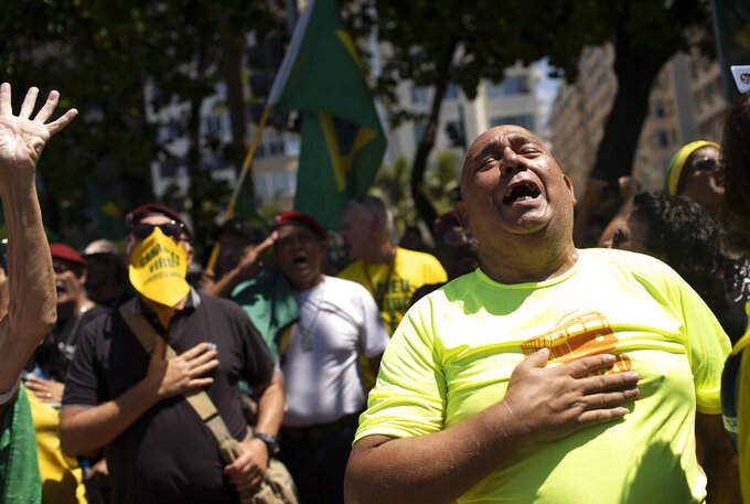 Supporters of Brazil's President Jair Bolsonaro rally on Copacabana beach, Rio de Janeiro, Brazil, Sunday, March 15, 2020. Thousands took to the streets on Sunday to demonstrate in favor of Bolsonaro, challenging in some states the ban on agglomerations due to coronavirus and ignoring his suggestion to postpone the acts. (AP Photo/Silvia Izquierdo)