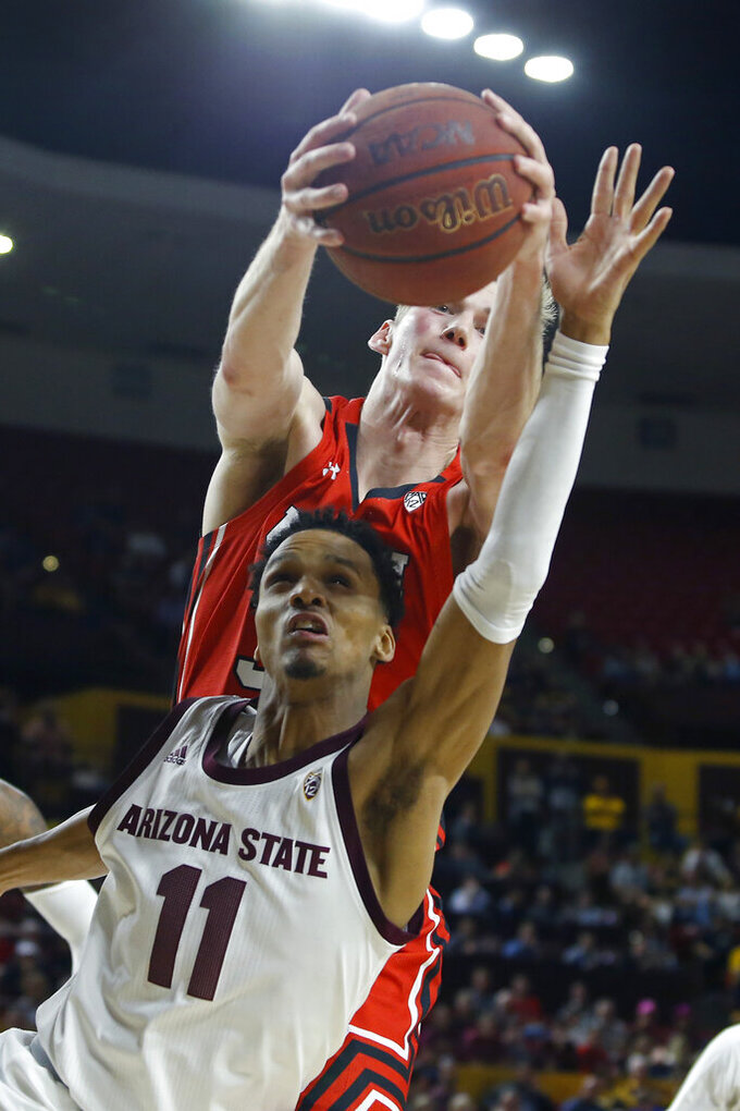 Utah center Branden Carlson, top, grabs a rebound over Arizona State guard Alonzo Verge during the first half of an NCAA college basketball game Saturday, Jan. 18, 2020, in Tempe, Ariz. (AP Photo/Ralph Freso)