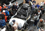 Residents look at a car that was destroyed in a bombing, in the southern port city of Sidon, Lebanon, Sunday, Jan 14, 2018. The Lebanese military said the bomb went off in a car in southern Lebanon, wounding its Palestinian owner. It was not immediately clear who carried out Sunday's bombing in the city of Sidon or why the Palestinian, identified as Mohammed Hamdan, was targeted. (AP Photo/Mohammed Zaatari)