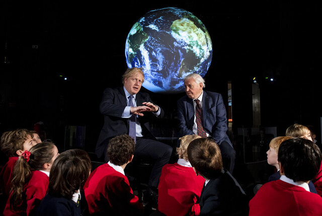 Britain's Prime Minister Boris Johnson, left, and David Attenborough speak with school children during the launch of the upcoming UK-hosted COP26 UN Climate Summit in London, Tuesday Feb. 4, 2020, that will take place in autumn 2020 in Glasgow, Scotland. Johnson is expected to announce a target to stop selling new petrol and diesel vehicles by 2035, including hybrid vehicles for the first time. (Chris J Ratcliffe/Pool via AP)