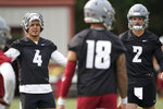 FILE - Washington State quarterbacks Jayden de Laura (4), Cammon Cooper (2), and Jarrett Guarantano (18) stand together on the first day of NCAA college football practice in Pullman, Wash., in this Friday, Aug. 6, 2021, file photo. WSU head coach Nick Rolovich would like for attention going into the 2021 season to be focused on players on the field, but he is getting just as much attention around his decision not to receive a COVID-19 vaccination.(AP Photo/Ted S. Warren, File)