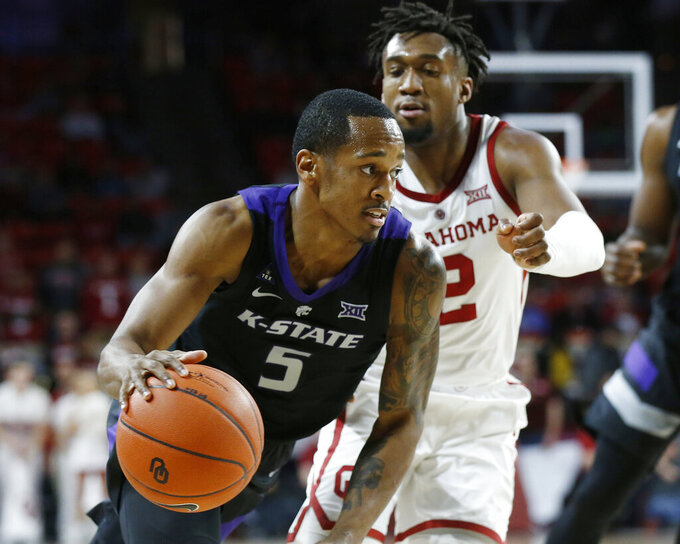 Kansas State guard Barry Brown Jr. (5) drives past Oklahoma guard Aaron Calixte (2) during the first half of an NCAA college basketball game in Norman, Okla., Wednesday, Jan. 16, 2019. (AP Photo/Sue Ogrocki)