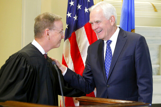 John O'Connor, right, talks with Oklahoma Supreme Court Justice M. John Kane IV after being sworn in as Oklahoma's new attorney general at the state Capitol in Oklahoma City, Friday, July 23, 2021. Gov. Kevin Stitt named 66-year-old O'Connor to the post on Friday after a two-month search. (Bryan Terry/The Oklahoman via AP)