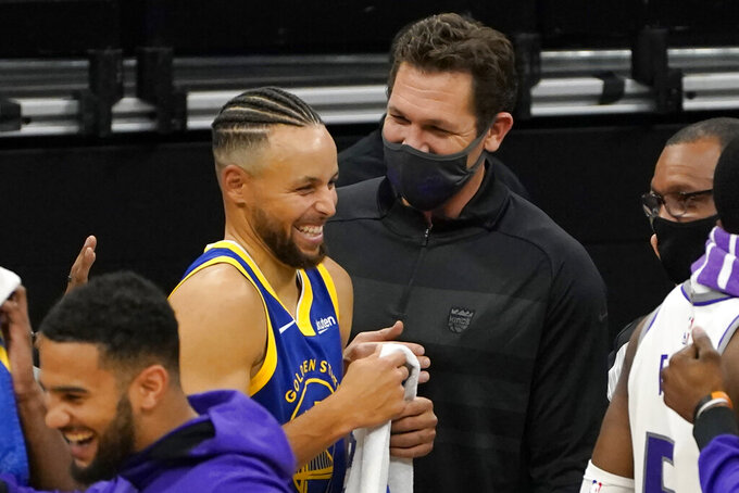 Golden State Warriors guard Stephen Curry, center left, laughs during a conversation with Sacramento Kings head coach Luke Walton after the Warriors beat the Kings 113-109 in an NBA preseason basketball game in Sacramento, Calif., Thursday, Dec. 17, 2020. (AP Photo/Rich Pedroncelli)