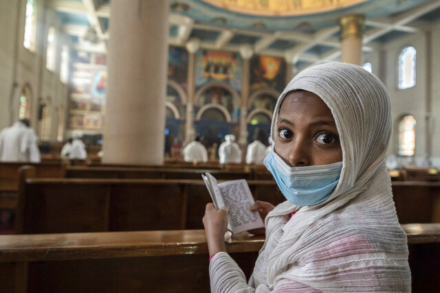 A girl wears a face mask to curb the spread of the coronavirus as she attends a prayer ceremony to mark the holiday of