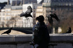 A woman looks at crows on a bridge in Paris, Tuesday, March 24, 2020. French President Emmanuel Macron urged employees to keep working in supermarkets, production sites and other businesses that need to keep running amid stringent restrictions of movement due to the rapid spreading of the new coronavirus in the country. For most people, the new coronavirus causes only mild or moderate symptoms. For some it can cause more severe illness, especially in older adults and people with existing health problems. (AP Photo/Francois Mori)