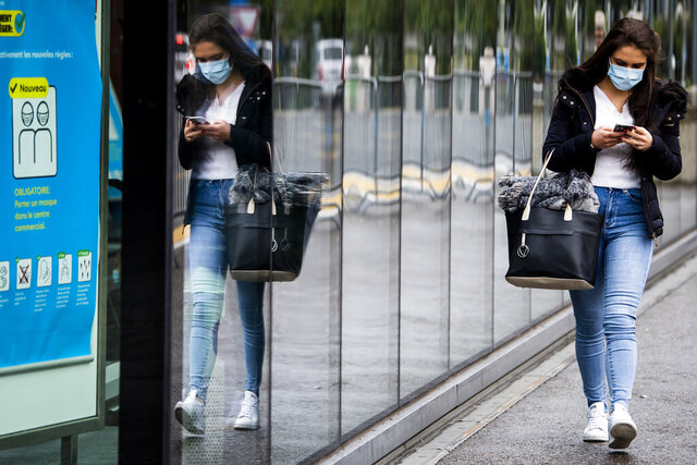 """A woman wearing a protective mask walks in front of a FOPH poster in front of a shopping centre in Fribourg, Switzerland, Friday, Oct. 16, 2020. Europe is at a """"turning point"""" in the fight against the coronavirus, said Bertrand Levrat, head of Switzerland's biggest hospital complex, acknowledging growing public fatigue over anti-COVID measures but says people must buckle down as Switzerland grapples with record daily case counts with measures like limiting the size of gatherings and stripping soldiers of weekend leave. (Jean-Christophe Bott/Keystone via AP)"""