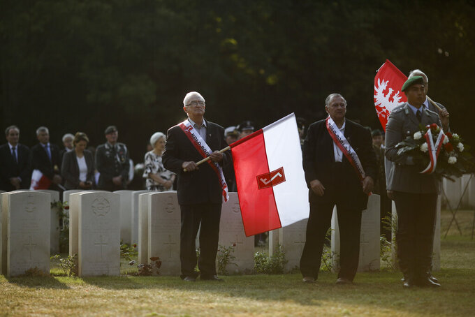 FILE - In this Sunday, Sept. 1, 2019 file photo, people with Polish flags attend a wreath laying ceremony to commemorate the Nazi-German invasion of Poland and the beginning of WWII, 80-years ago, at the British War Cemetery in Berlin, Germany.A memorial in Berlin to the Polish victims of World War II has moved a step closer to realization, and Germany's foreign minister said Wednesday that construction should start during the next German parliament's four-year term. Nazi Germany invaded Poland in 1939 and subjected its population to more than five years of brutal occupation. Around 3 million of the country's 3.3 million Jews were murdered, as were more than 2 million other mostly Christian Poles. (AP Photo/Markus Schreiber, File)