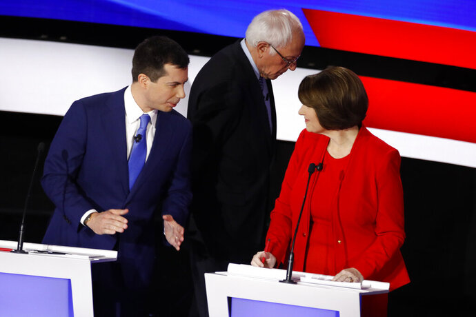 Democratic presidential candidates former South Bend Mayor Pete Buttigieg, left, and Sen. Amy Klobuchar, D-Minn., talk while Sen. Bernie Sanders, I-Vt., heads off stage at a break Tuesday, Jan. 14, 2020, during a Democratic presidential primary debate hosted by CNN and the Des Moines Register in Des Moines, Iowa. (AP Photo/Patrick Semansky)
