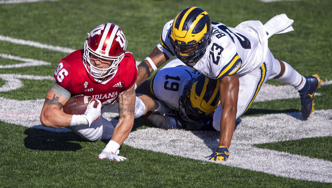 Indiana tight end Peyton Hendershot (86) dives for first-down yardage as he's stopped by Michigan defensive lineman Kwity Paye (19) and linebacker Michael Barrett (23) during the second half of an NCAA college football game Saturday, Nov. 7, 2020, in Bloomington, Ind. Indiana won 38-21. (AP Photo/Doug McSchooler)