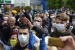People, some wearing face masks to protect against coronavirus, listen to a speaker as they gather to give signatures in support of potential presidential candidates in  the upcoming presidential elections in Minsk, Belarus, Sunday, May 24, 2020. The presidential campaign is underway in Belarus despite the coronavirus outbreak after the parliament and government refused to postpone the election scheduled for August 9. (AP Photo/Sergei Grits)