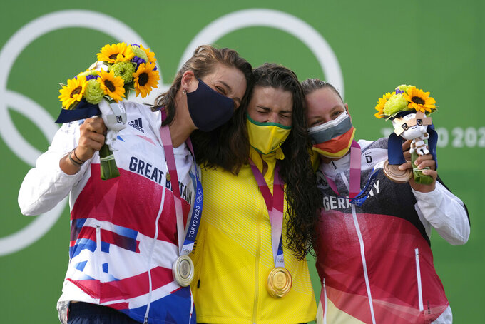 Jessica Fox of Australia, centre, holds the gold medal Mallory Franklin of Britain, left, holds the silver medal and Andrea Herzog of Germany, right, with the bronze medal in the Women's C1 of the Canoe Slalom at the 2020 Summer Olympics, Thursday, July 29, 2021, in Tokyo, Japan. (AP Photo/Kirsty Wigglesworth)