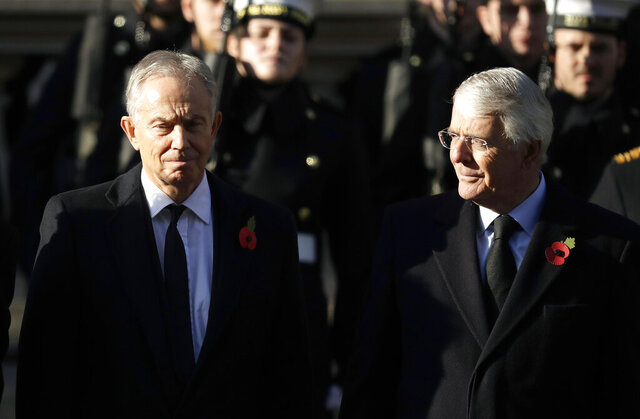 FILE - In this Sunday, Nov. 10, 2019 file photo, former British Prime Ministers Tony Blair, left and John Major attend the Remembrance Sunday ceremony at the Cenotaph in Whitehall in London. Remembrance Sunday is held each year to commemorate the service men and women who fought in past military conflicts. The two former British prime ministers who played crucial roles in bringing peace to Northern Ireland joined forces Sunday, Sept. 13, 2020 to urge lawmakers to reject government plans to over-ride the Brexit deal with the European Union, arguing that it imperils that peace as well as damaging the U.K.'s reputation.  (AP Photo/Matt Dunham, File)