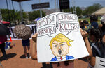 A demonstrator holds a sign to protest the visit of President Donald Trump to the border city after the Aug. 3 mass shooting in El Paso, Texas, Wednesday, Aug. 7, 2019.  Trump headed to El Paso, after visiting  Dayton, Ohio on Wednesday to offer a message of healing and unity, but he will be met by unusual hostility in both places by people who fault his own incendiary words as a contributing cause to the mass shootings.  (AP Photo/Andres Leighton)
