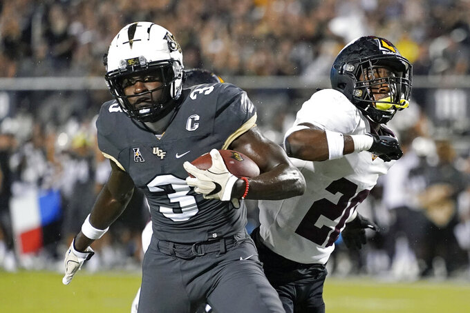 Central Florida wide receiver Brandon Johnson (3) scores a touchdown past Bethune-Cookman cornerback Omari Hill-Robinson, right, during the first half of an NCAA college football game Saturday, Sept. 11, 2021, in Orlando, Fla. (AP Photo/John Raoux)