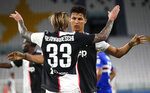 Juventus' Federico Bernardeschi, left, is congratulated by teammate Cristiano Ronaldo after scoring his team's second goal during the Serie A soccer match between Juventus and Sampdoria at the Allianz stadium in Turin, Italy, Sunday, July 26, 2020. (AP Photo/Antonio Calanni)